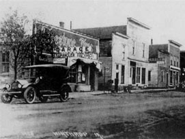 old black and white image of a car next to the garage