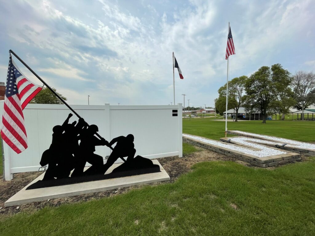iwa jima metal sculpture with flag flying